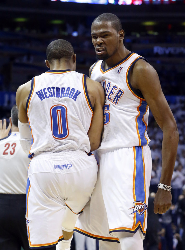 Photo - Oklahoma City Thunder forward Kevin Durant (35) bumps chests with teammate Russell Westbrook (0) in the third quarter of Game 2 in their first-round NBA basketball playoff series against the Houston Rockets in Oklahoma City, Wednesday, April 24, 2013. Oklahoma City won 105-102. (AP Photo/Sue Ogrocki)