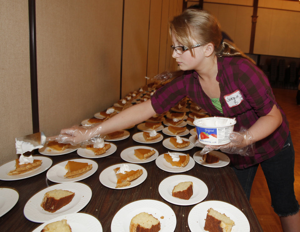 Volunteer Joezie Cook, 12, puts whip cream on pies during the Edmond Community Thanksgiving event at The University of Central Oklahoma in  Edmond, Thursday  November 22, 2012. Photo By Steve Gooch, The Oklahoman