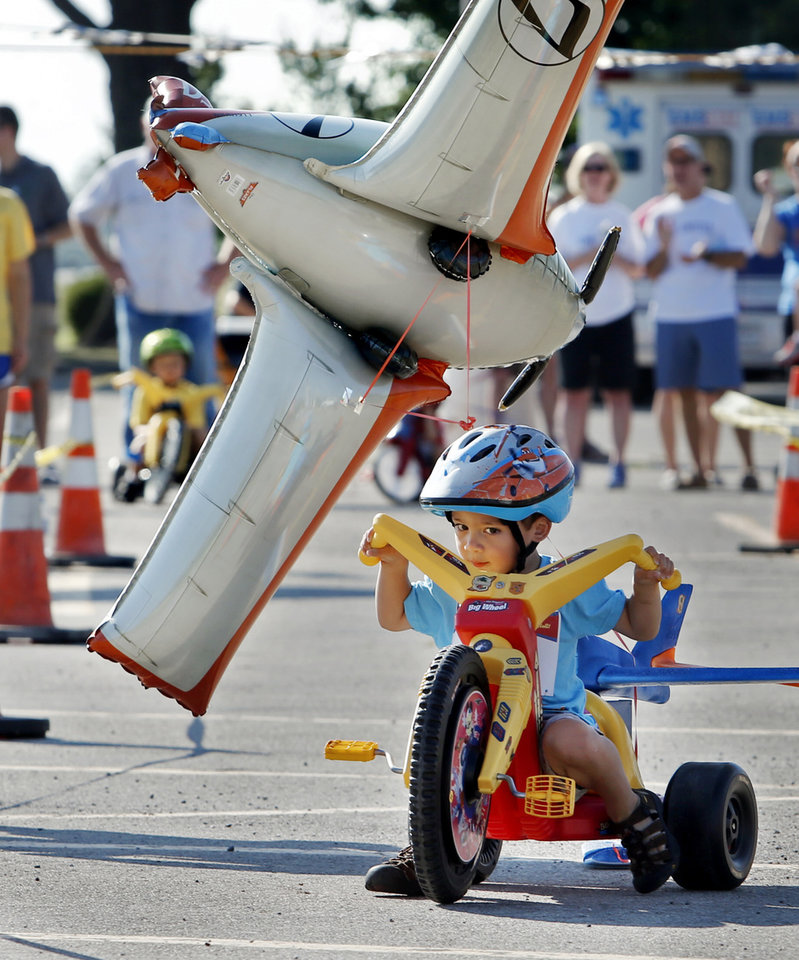 Photo -  Isaac Ozeraglu, 3, pulls a balloon behind his tricycle as he participates in The Ride, a big-wheel race for children in Norman on Saturday that benefited United Way. PHOTO BY STEVE SISNEY, THE OKLAHOMAN   STEVE SISNEY -