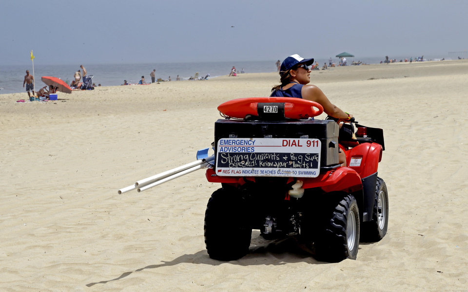 Photo - A lifeguard patrols the beach in Nags Head, N.C., Thursday, July 3, 2014. Hurricane Arthur is forecast to pass by Hatteras on Friday morning. The island is under mandatory evacuation orders. (AP Photo/Gerry Broome)