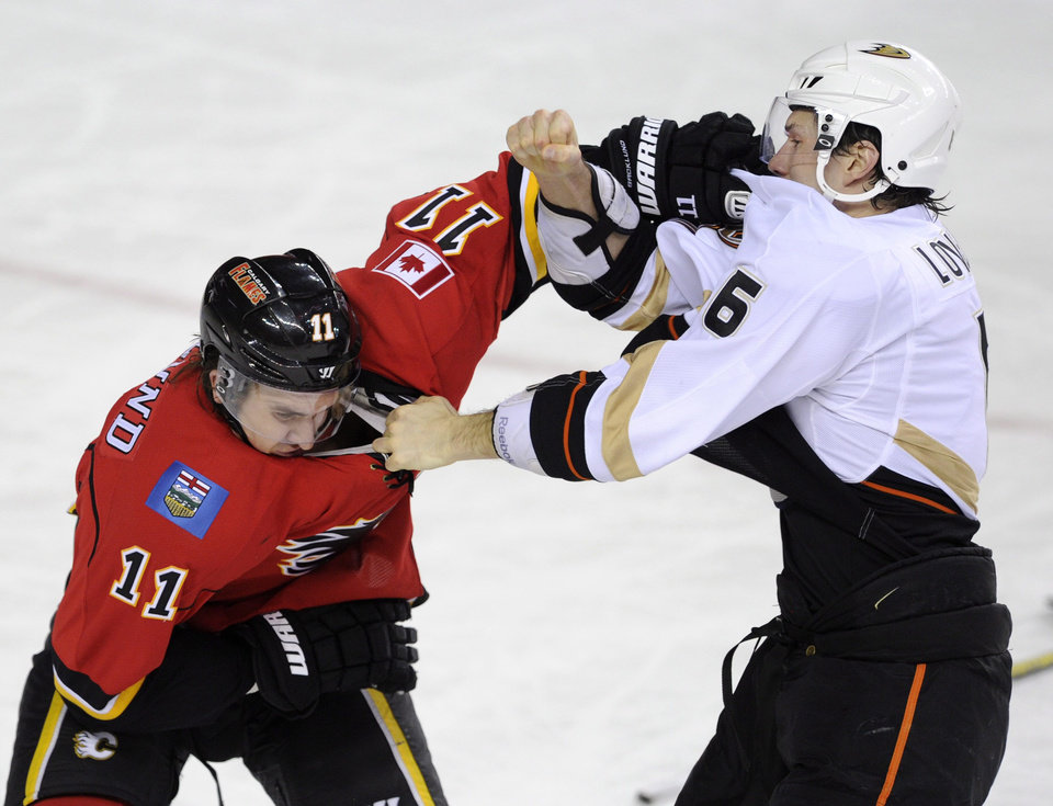 Anaheim Ducks\' Ben Lovejoy, right, briefly fights with Calgary Flames\' Mikael Backlund, from Sweden, during first period NHL action in Calgary, Alberta, Friday, April 19, 2013. (AP Photo/The Canadian Press, Larry MacDougal)
