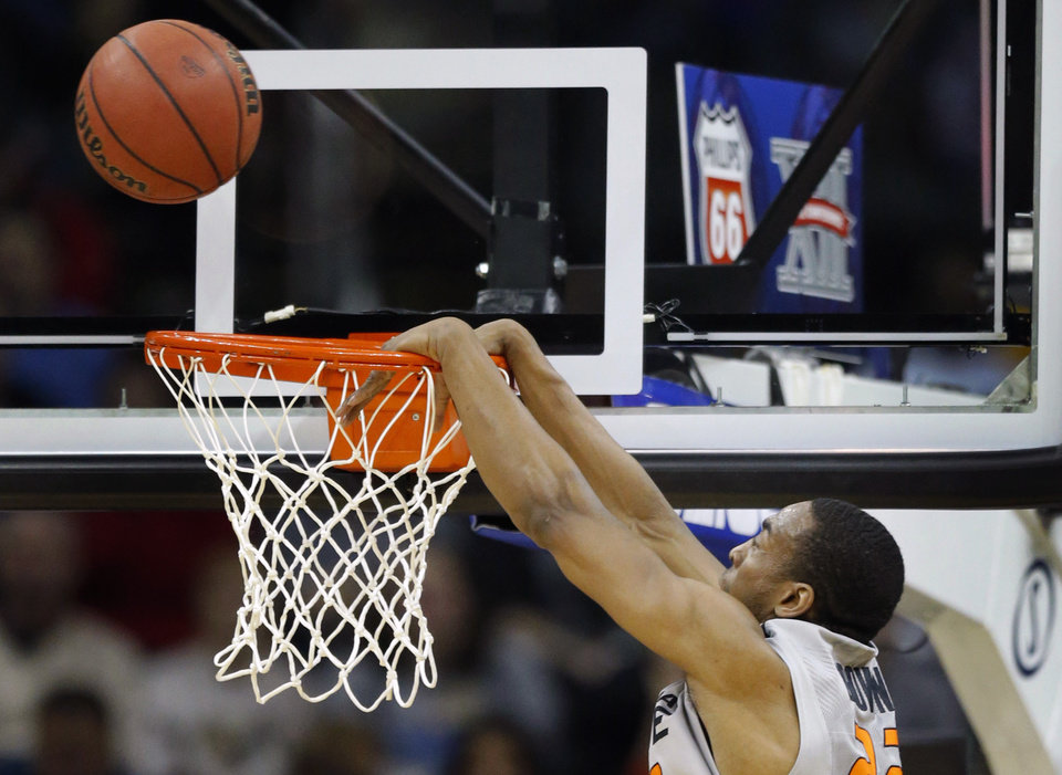 Photo - Oklahoma State guard Markel Brown (22) misses a dunk during the first half of an NCAA college basketball game against Texas Tech in the Big 12 men's tournament in Kansas City, Mo., Wednesday, March 12, 2014. Brown was fouled on the play. (AP Photo/Orlin Wagner)