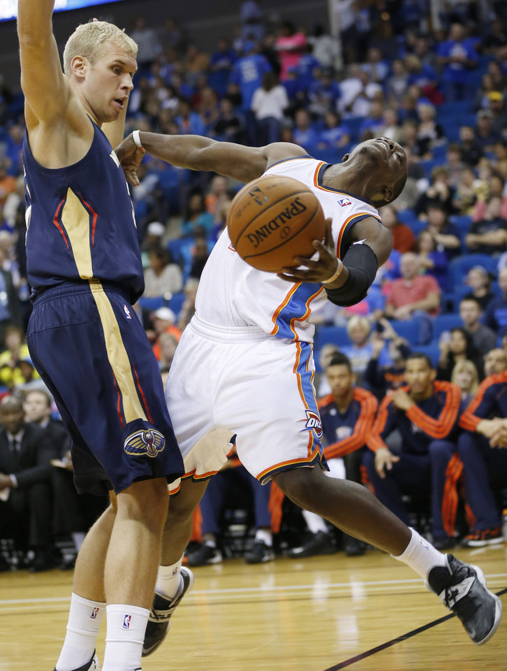 Photo - Oklahoma City Thunder guard Reggie Jackson, right, is fouled by New Orleans Pelicans center Greg Stiemsma during the third quarter of an NBA basketball preseason game in Tulsa, Okla., Thursday, Oct. 17, 2013. New Orleans won 105-102. (AP Photo/Sue Ogrocki) ORG XMIT: OKSO118