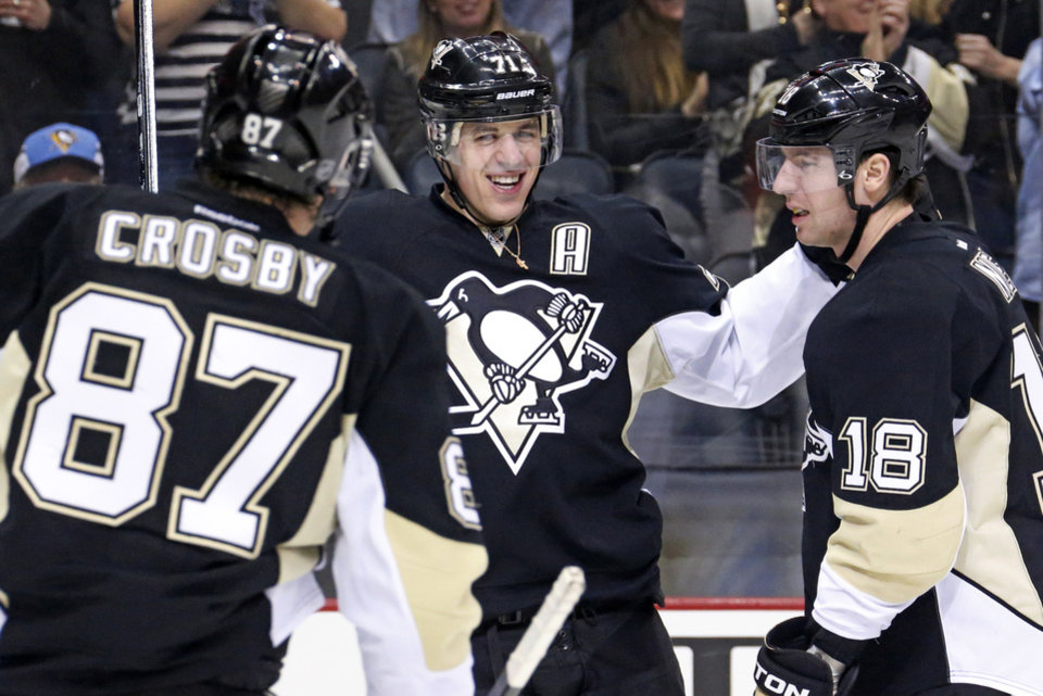 Photo - Pittsburgh Penguins' Evgeni Malkin (71) celebrates his goal with James Neal (18), and Sidney Crosby (87) during the second period of an NHL hockey game against the New York Rangers in Pittsburgh, Friday, Feb. 7, 2014. (AP Photo/Gene J. Puskar)