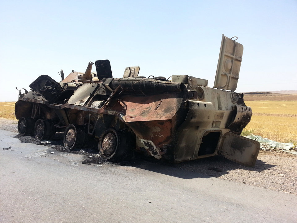 Photo - A burned Iraqi Army armored vehicle sits outside Beiji refinery, some 250 kilometers (155 miles) north of Baghdad, Iraq, Thursday, June 19, 2014. The fighting at Beiji comes as Iraq has asked the U.S. for airstrikes targeting the militants from the Islamic State of Iraq and the Levant. While U.S. President Barack Obama has not fully ruled out the possibility of launching airstrikes, such action is not imminent in part because intelligence agencies have been unable to identify clear targets on the ground, officials said. (AP Photo)