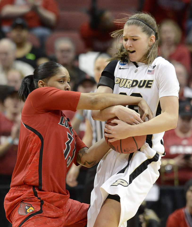 Louiosville's Monique Reid, left, battles Purdue's Sam Ostarello for a the ball during the first half of their second round game in the women's NCAA college basketball tournament in Louisville, Ky., Tuesday March 26, 2013. (AP Photo/Timothy D. Easley)