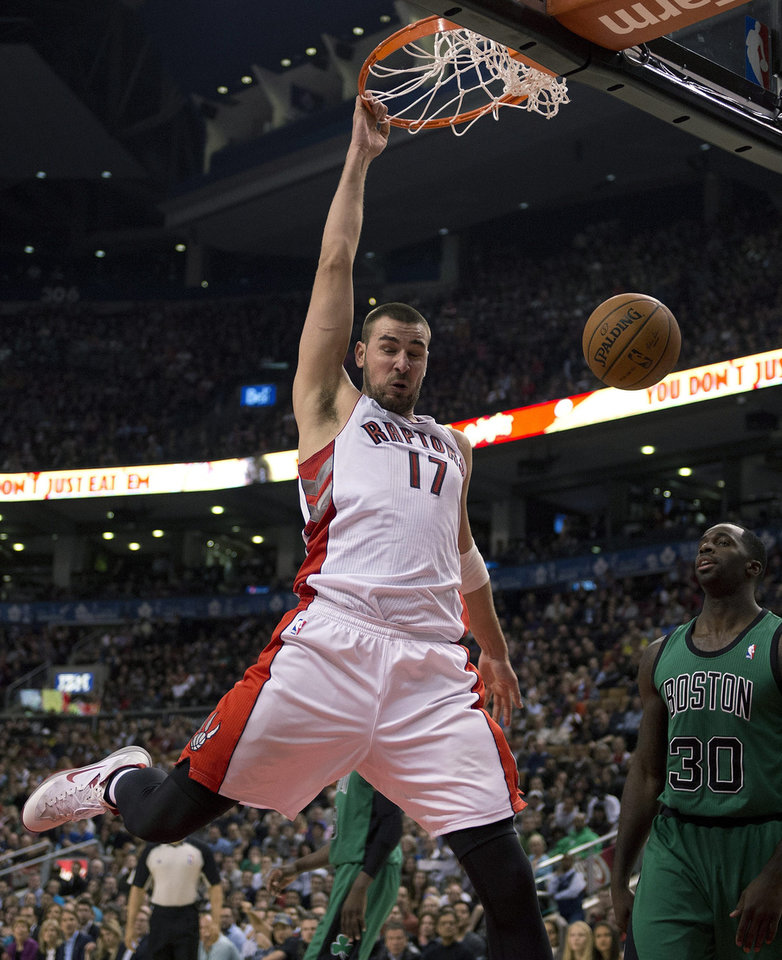 Photo - Toronto Raptors centre Jonas Valanciunas (17) slams home a dunk against Boston Celtics forward Jeff Green (8) during first half NBA action in Toronto on Friday March 28, 2014. (AP Photo/The Canadian Press, Frank Gunn)