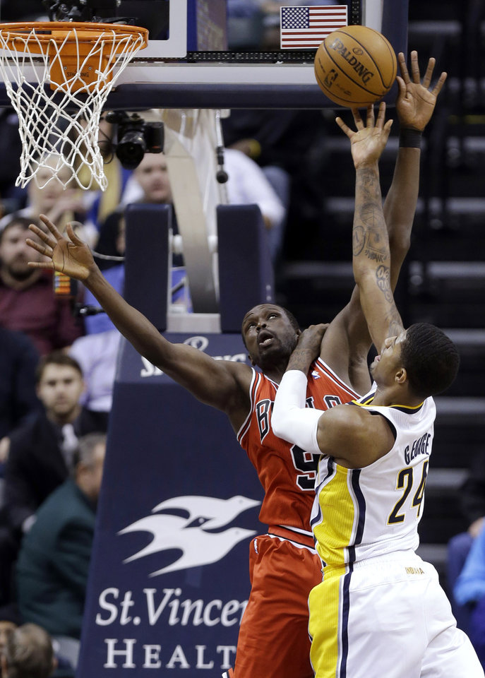 Photo - Indiana Pacers forward Paul George, right, holds down Chicago Bulls forward Luol Deng as he shoots in the first half of an NBA basketball game in Indianapolis, Monday, Feb. 4, 2013.  (AP Photo/Michael Conroy)