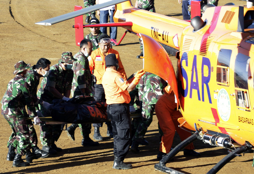 Photo -   Indonesian soldiers load a victim of Wednesday's plane crash on to a helicopter at Cijeruk on Mount Salak , in Bogor, West Java, Indonesia, Sunday, May 13, 2012. Clearer weather finally allowed Indonesian helicopters to land Saturday and retrieve some remains of the 45 people aboard a Russian-made plane that crashed into the volcano during a demonstration flight. (AP Photo/Achmad Ibrahim)