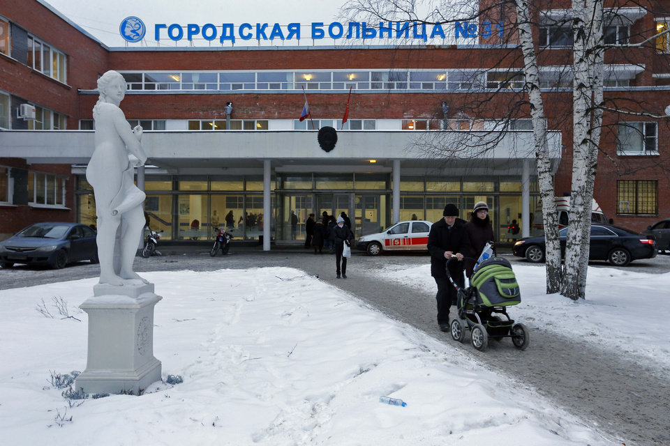 Photo - People walk at City Hospital No. 31 in St. Petersburg, Russia, Wednesday, Jan. 23, 2013. Russian officials on Wednesday backed off on a plan to shut a clinic specialized in treating children with cancer in order to turn it into a medical center for the nation's top judges, marking a rare occasion when authorities seemed to bow to public pressure. The authorities intention to turn City Hospital No. 31 into a clinic that would exclusively serve judges of Russia's top courts, which are being relocated to St.Petersburg from Moscow, has caused a strong public dismay. (AP Photo/Dmitry Lovetsky)