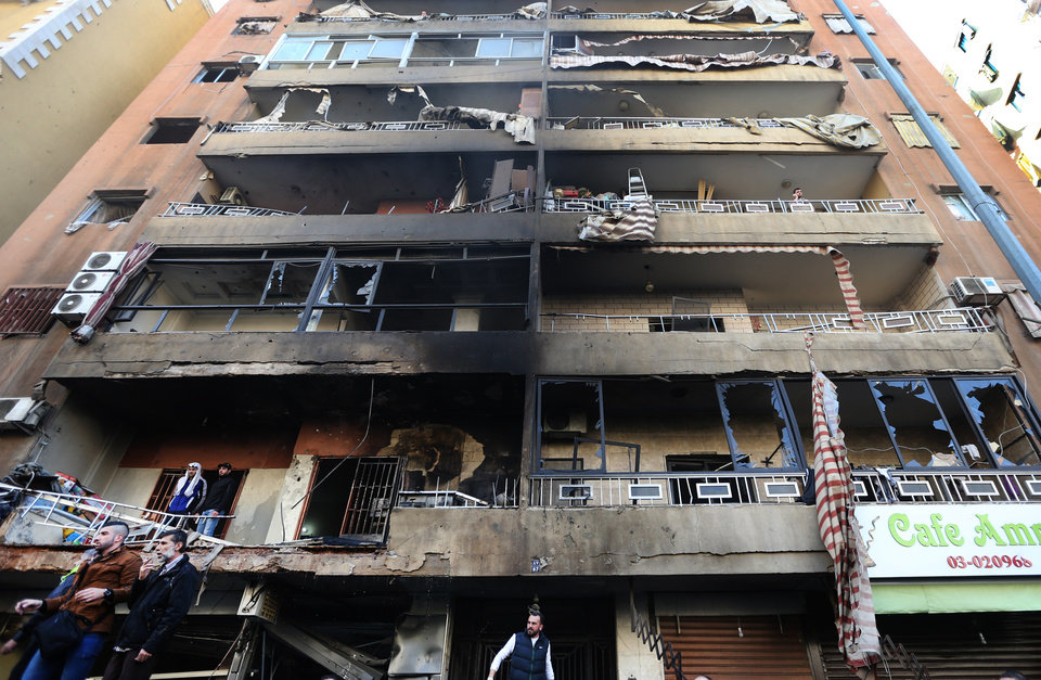 Photo - Lebanese citizens stand in front of a damaged building at the site of an explosion in the southern suburb of Beirut, Lebanon, Tuesday, Jan. 21, 2014. A car bomb ripped through a Shiite neighborhood in southern Beirut killing several people and setting plumes of smoke over the area in the latest attack targeting supporters of the militant Hezbollah group in Lebanon. (AP Photo/Hussein Malla)