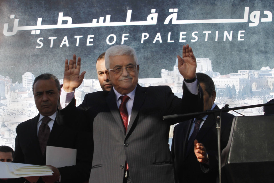 Photo - Palestinian President Mahmoud Abbas, waves to the crowd during celebrations for their successful bid to win U.N. statehood recognition in the West Bank city of Ramallah, Sunday, Dec. 2, 2012. Abbas returned home to a hero's welcome after winning a resounding endorsement for Palestinian independence at the United Nations. Israel on Sunday roundly rejected the United Nations' endorsement of an independent state of Palestine, announcing it would withhold more than $100 million collected for the Palestinian government to pay debts to Israeli companies.  (AP Photo/Nasser Shiyoukhi)