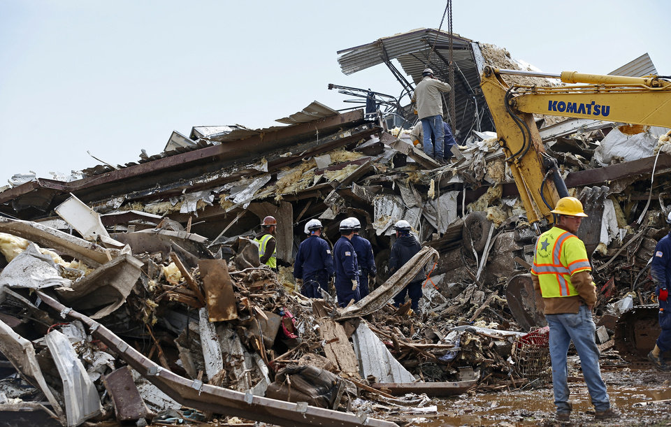 Photo - Workers continue going through the debris at the Plaza Towers Elementary School in Moore, Okla., on Tuesday, May 21, 2013. A tornado hit the area on Monday, May 20, 2013.  (AP Photo/The Oklahoman, Bryan Terry)