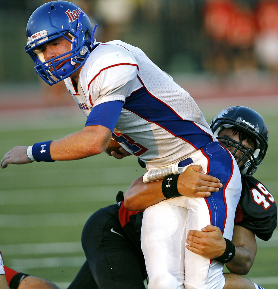 Photo - Moore's Grant Linstead is tackled by Westmoore's Sijon Rider during their high school football game at Moore Stadium in Moore, Oklahoma on Friday, September 2, 2011. Photo by John Clanton, The Oklahoman