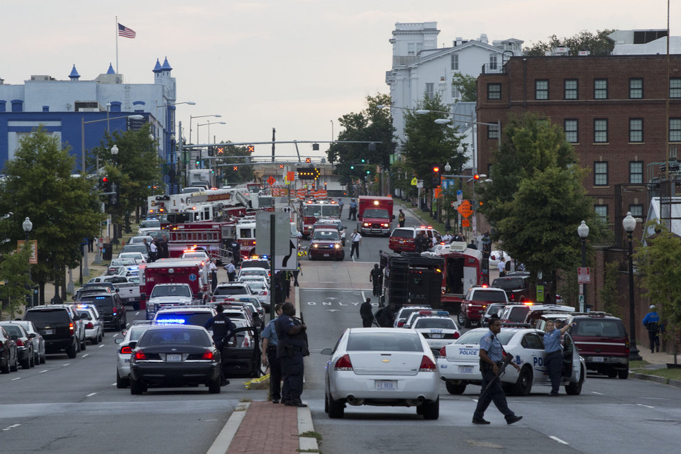 Photo - Police work the scene on M Street, SE in Washington, where a gunman was reported at the Washington Navy Yard in Washington, on Monday, Sept. 16, 2013. The U.S. Navy says one person is injured after a shooting at a Navy building in Washington.  (AP Photo/Jacquelyn Martin)