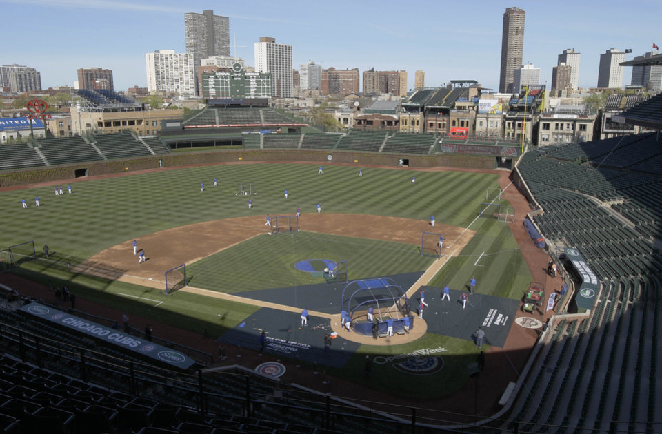 Photo - FILE - In this April 4, 2012, file photo, Chicago Cubs players work out at Wrigley Field in Chicago, the day before their opening day baseball game against the Washington Nationals. Chicago's Wrigley Field, New Orleans' Saenger Theatre and a historic Los Angeles' shipbuilding center have joined a list of sites being saved thanks to the efforts of historic preservationists in 2013. (AP Photo/Nam Y. Huh, File)