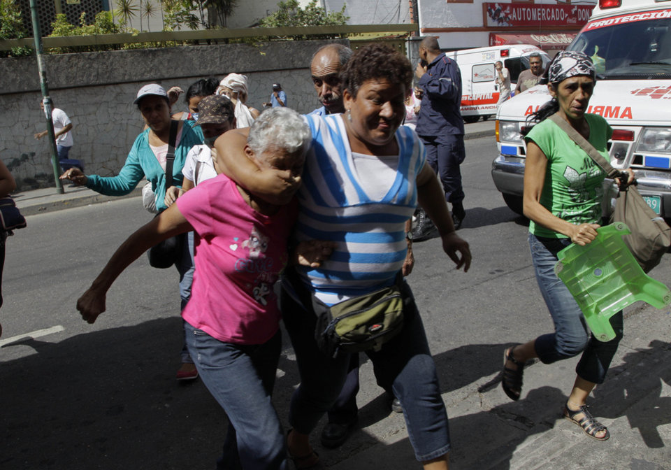 Photo -   Relatives of inmates protesting against measures taken by authorities to control a riot at the La Planta prison run from tear gas fired by National Guard soldiers during clashes outside the jail in Caracas, Venezuela, Thursday, May 17, 2012. Gunfire erupted on Thursday inside the prison where armed inmates have prevented security forces from retaking control for nearly three weeks. (AP Photo/Ariana Cubillos)