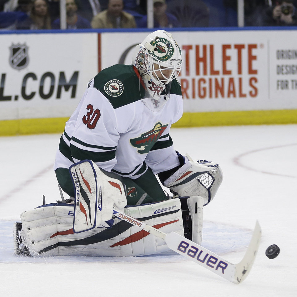 Photo - Minnesota Wild goalie Ilya Bryzgalov makes a save during the second period of the NHL hockey game against the New York Islanders, Tuesday, March 18, 2014, in Uniondale, New York. (AP Photo/Seth Wenig)