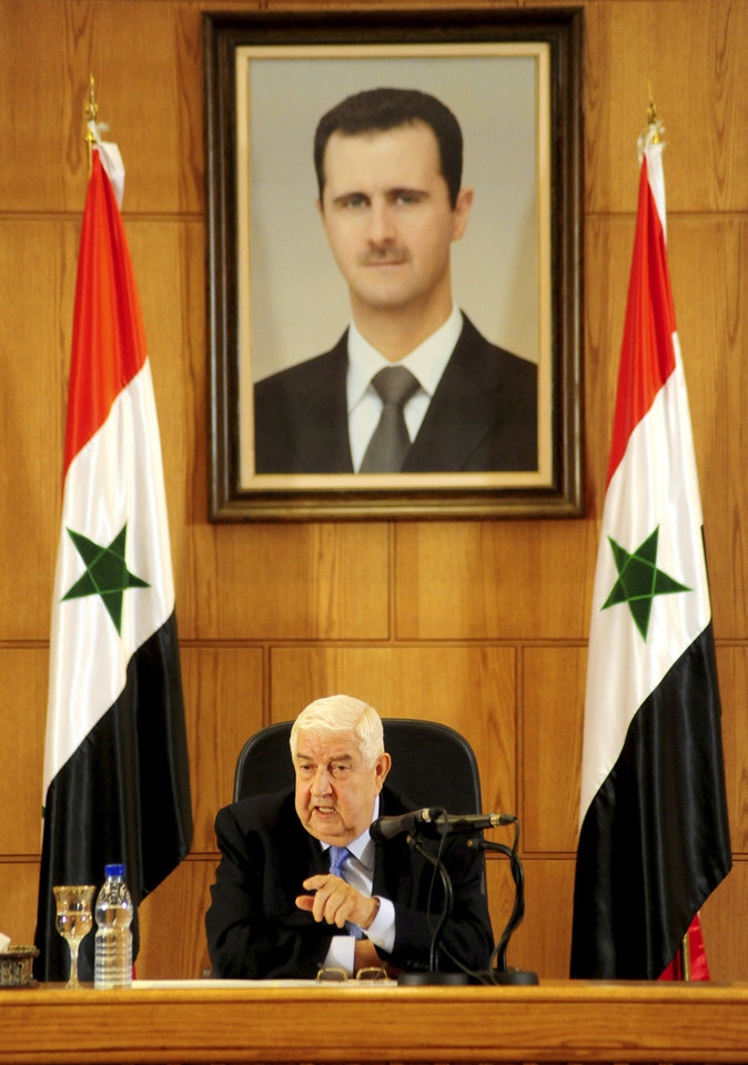 Photo - In this photo released by the Syrian official news agency SANA, Syrian Foreign Minister Walid al-Moallem speaks during a press conference, giving the first public comments by a senior Assad official on the threat posed by the Islamic State group, in Damascus, Syria on Monday, August 25, 2014. Al-Moallem warned the U.S. not to conduct airstrikes inside Syria against the Islamic State group without Damascus' consent, saying any such attack would be considered an aggression. Al-Moallem also said that Syria is ready to work with regional states and the international community amid the onslaught of Islamic militants there and in Iraq, adding that the Syrian government is a crucial partner in the war on terror. (AP Photo/SANA)