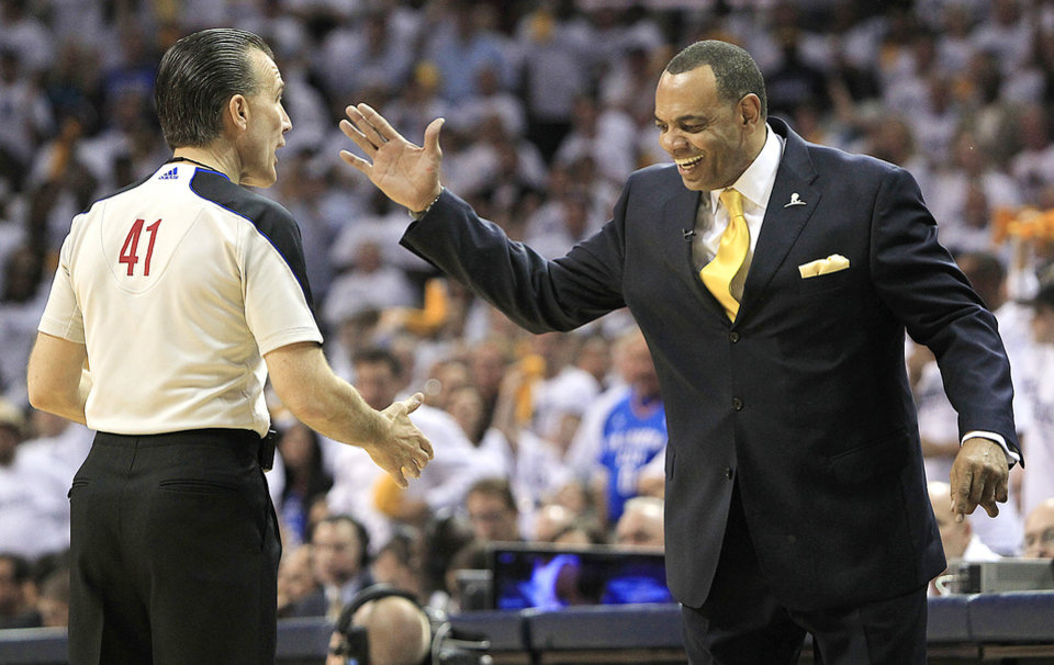 Photo - Memphis Grizzlies head coach Lionel Hollins, right, slaps hands with referee Ken Mauer (41) during the second half of Game 3 against the Oklahoma City Thunder in a second-round NBA basketball series on Saturday, May 7, 2011, in Memphis, Tenn. The Grizzlies won 101-93 in overtime to take a 2-1 lead in the series. (AP Photo/Mark Humphrey) ORG XMIT: TNMH120