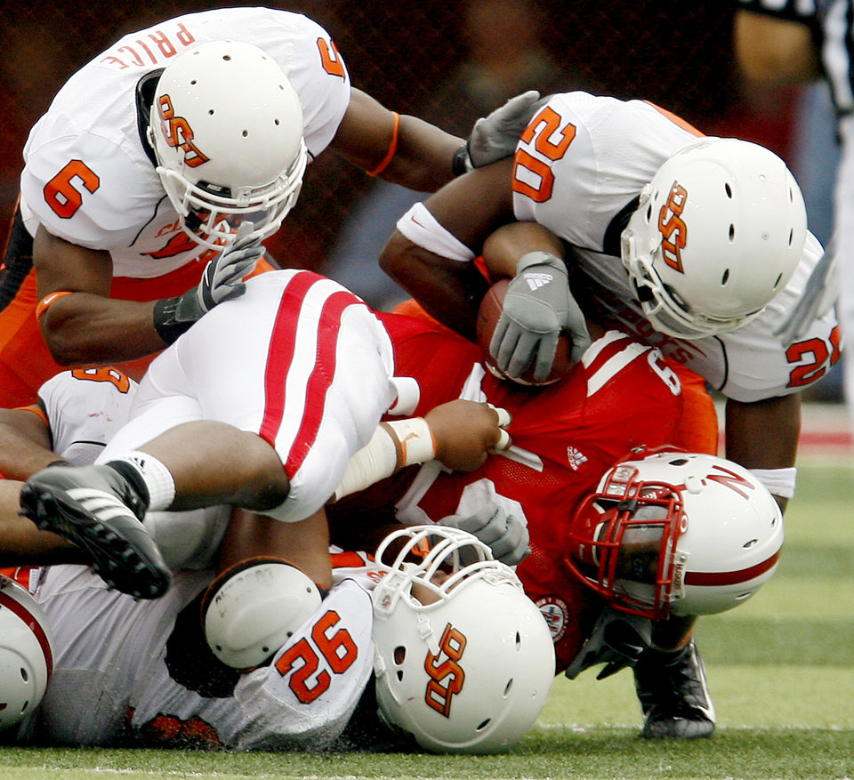Photo - Jeremy Broadway, left, Tonga Tea Jr., and Andre Sexton of OSU tackle Quentin Castille of Nebraska during  the college football game between Oklahoma State University (OSU) and the University of Nebraska at Memorial Stadium in Lincoln, Neb., on Saturday, Oct. 13, 2007. By Bryan Terry, The Oklahoman    ORG XMIT: KOD