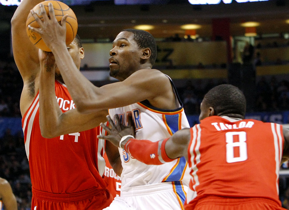 Photo - Oklahoma City's Kevin Durant takes the ball past Houston's Jermaine Taylor and Chuck Hayes during their NBA basketball game at the OKC Arena in downtown Oklahoma City on Wednesday, Nov. 17, 2010. Photo by John Clanton, The Oklahoman