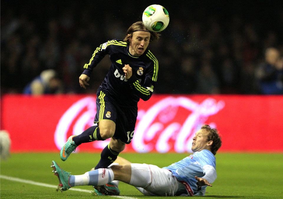 Real Madrid Luka Modric from Croatia, left, heads on the ball while being tackled by Celta's Michael Krohn-Dehli from Denmark during the 1st leg of a last-16 Copa del Rey soccer match at the Balaídos stadium in Vigo, Spain, Wednesday, Dec. 12, 2012. (AP Photo/Lao R. Villar)