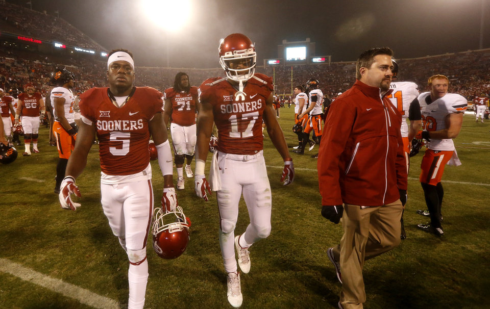 Photo - Durron Neal (5) and Oklahoma's Jordan Smallwood (17) walk off the field following  the Bedlam college football game between the University of Oklahoma Sooners (OU) and the Oklahoma State Cowboys (OSU) at Gaylord Family-Oklahoma Memorial Stadium in Norman, Okla., Saturday, Dec. 6, 2014. Photo by Sarah Phipps, The Oklahoman
