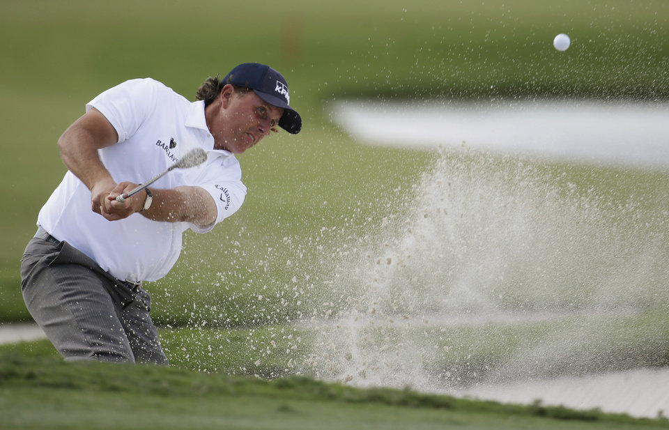 Photo - Phil Mickelson hits from a bunker on the ninth hole during the second round of the Cadillac Championship golf tournament, Friday, March 7, 2014, in Doral, Fla. (AP Photo/Lynne Sladky)