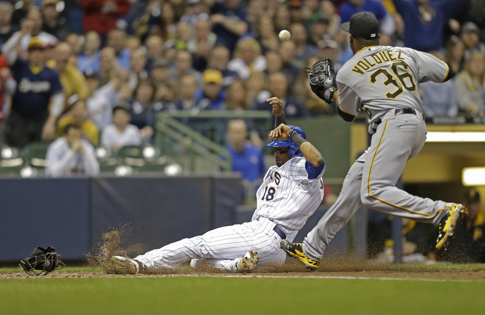 Photo - Milwaukee Brewers' Khris Davis (18) scores as Pittsburgh Pirates' starting pitcher Edinson Volquez takes the late throw during the second inning of a baseball game Saturday, April 12, 2014, in Milwaukee. Davis scored after a Volquez wild pitch. (AP Photo/Jeffrey Phelps)