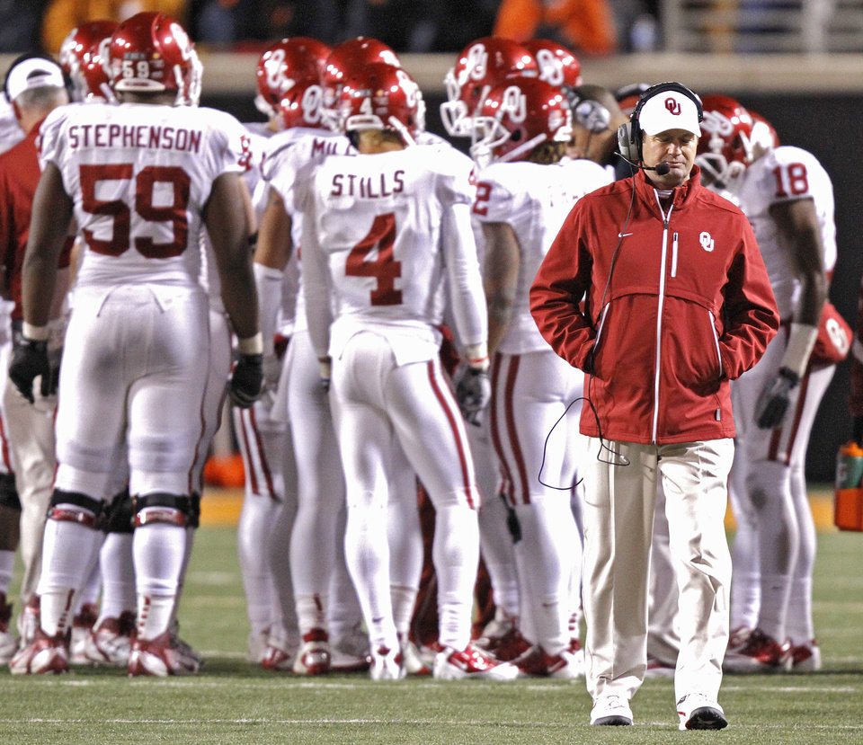 Coach Bob Stoops walks away from the huddle in the fourth quarter of the Sooners\' 44-10 loss to OSU during the Bedlam college football game between the Oklahoma State University Cowboys (OSU) and the University of Oklahoma Sooners (OU) at Boone Pickens Stadium in Stillwater, Okla., Saturday, Dec. 3, 2011. Photo by Chris Landsberger, The Oklahoman