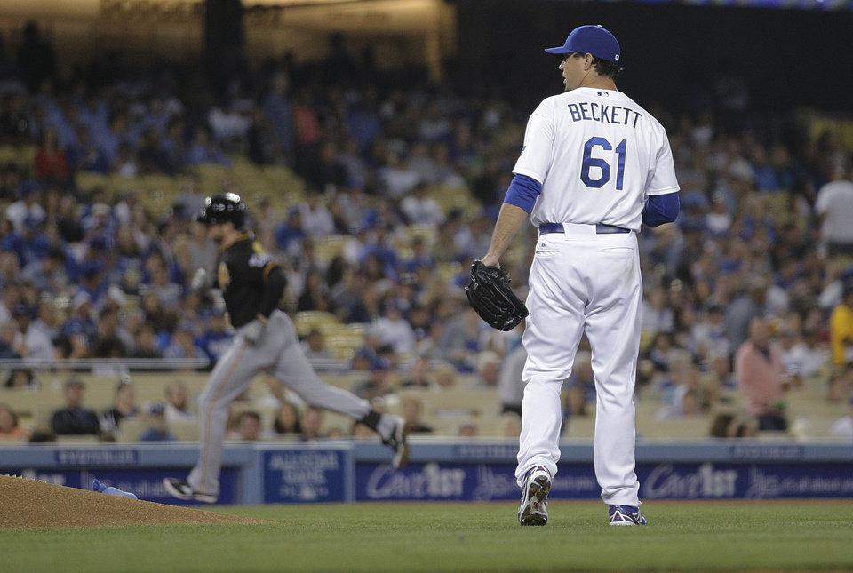 Photo - Los Angeles Dodgers starting pitcher Josh Beckett, right, stands near the mound as Pittsburgh Pirates' Ike Davis, background left, rounds the bases after hitting a home run during the fourth inning of a baseball game Friday, May 30, 2014, in Los Angeles. (AP Photo/Jae C. Hong)