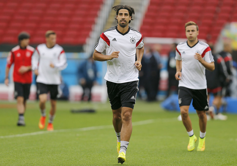 Photo - Germany's Sami Khedira, center, warms up with teammates  during a training session at the Estadio Beira-Rio Stadium in Porto Alegre, Brazil, Sunday, June {try}, 2014.  Germany will play Algeria in a World Cup round of 16 soccer match on June 30. (AP Photo/Frank Augstein)