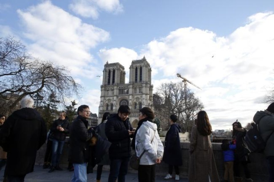 Photo -  People walk in front of Notre Dame cathedral Dec. 25 in Paris. [AP PHOTO]