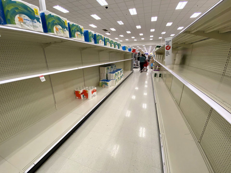 Photo - The shelves are almost bare in the bathroom tissue aisle at the Super Target at Memorial and Penn., Friday, March 13, 2020.  [Photo by Doug Hoke/The Oklahoman]