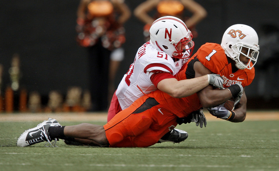 Photo - OSU's Joseph Randle is brought down by Nebraska's Will Compton during the college football game between the Oklahoma State Cowboys (OSU) and the Nebraska Huskers (NU) at Boone Pickens Stadium in Stillwater, Okla., Saturday, Oct. 23, 2010. Photo by Bryan Terry, The Oklahoman