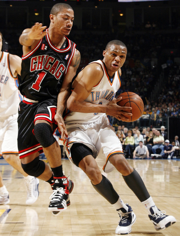 Oklahoma City's Russell Westbrook (0) drives the ball past Derrick Rose (1) of Chicago in the first half of the NBA basketball game between the Chicago Bulls and the Oklahoma City Thunder at the Ford Center in Oklahoma City, Wednesday, March 18, 2009. PHOTO BY NATE BILLINGS, THE OKLAHOMAN