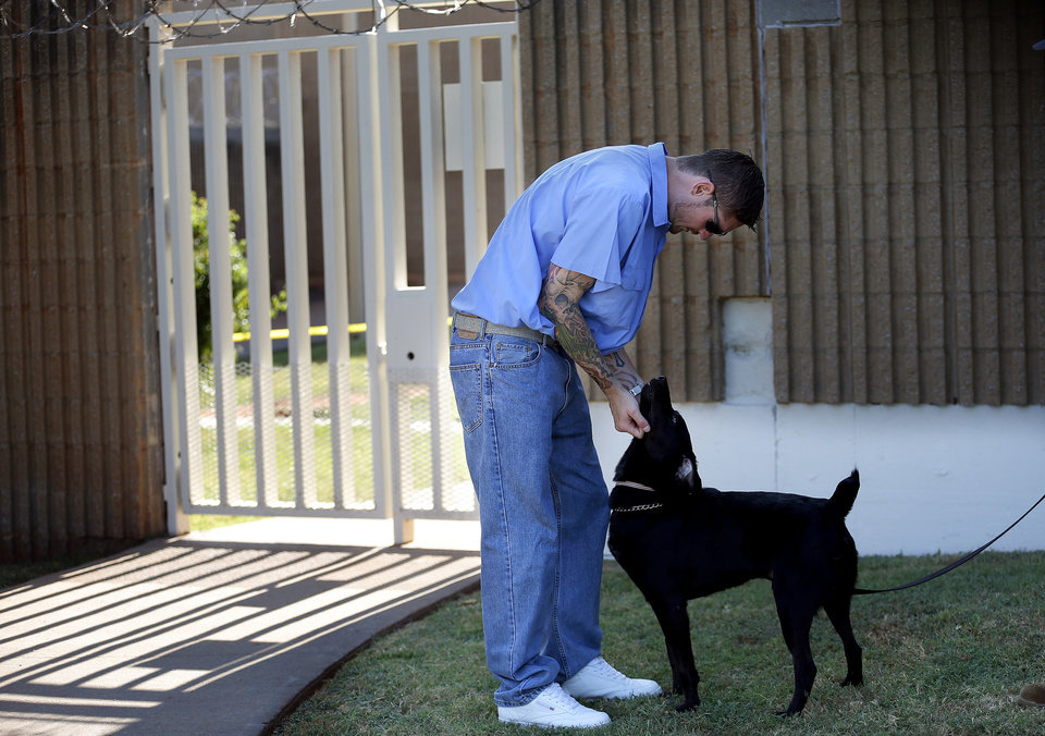 Photo -  Inmate Todd Saunders pets Dillard at the Lexington Assessment and Reception Center, Friday, July 11,  2013, in Lexington, Okla. Photo by Sarah Phipps, The Oklahoman