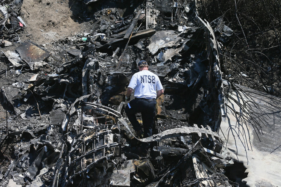 Photo - A National Transportation Safety Board official looks through the wreckage at the scene Monday, June 2, 2014, in Bedford, Mass., where a plane plunged down an embankment and erupted in flames during a takeoff attempt at Hanscom Field on Saturday night. Lewis Katz, co-owner of The Philadelphia Inquirer, and six other people died in the crash. (AP Photo/Boston Herald, Mark Garfinkel, Pool)