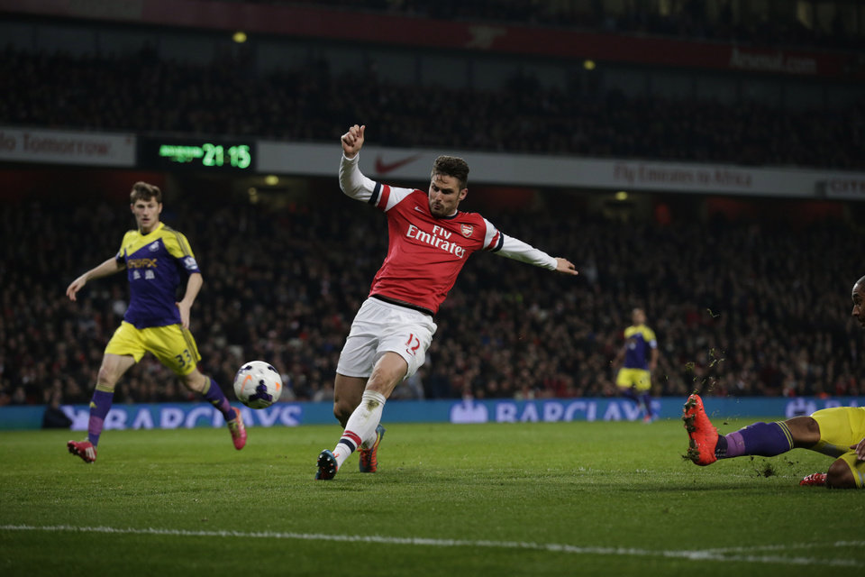 Photo - Arsenal's Olivier Giroud, center, scores his side's second goal during the English Premier League soccer match between Arsenal and Swansea City at the Emirates Stadium in London, Tuesday, March 25, 2014. (AP Photo/Matt Dunham)