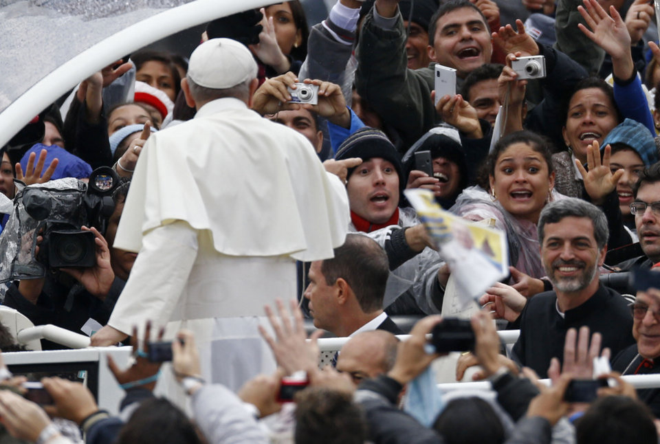 Photo - Pilgrims wave to Pope Francis as he arrives to the Aparecida Basilica in Aparecida, Brazil, Wednesday, July 24, 2013. Pope Francis, the first pontiff from the Americas, arrived to the basilica that holds Brazil's patron saint, the dark-skinned Virgin of Aparecida.  (AP Photo/Victor R. Caivano)