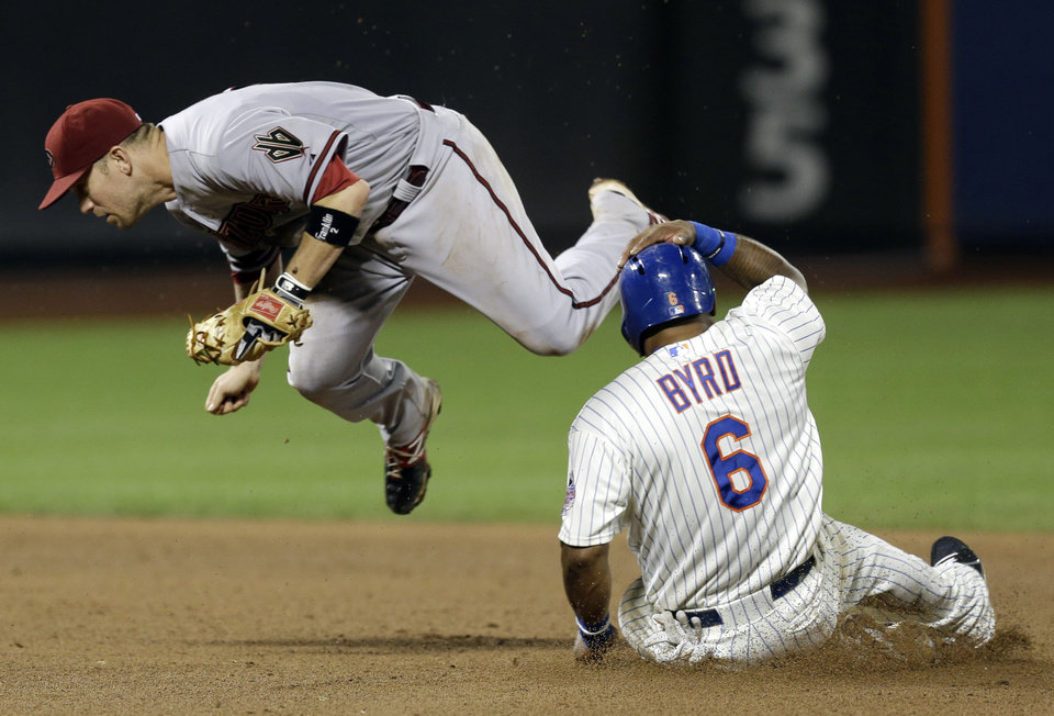 Photo - Arizona Diamondbacks' Aaron Hill, left, jumps after tagging second base before New York Mets' Marlon Byrd during the seventh inning of the baseball game at Citi Field, Monday, July 1, 2013, in New York. (AP Photo/Seth Wenig)
