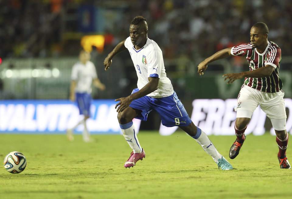 Italy's national soccer team player Mario Balotelli, left, dribbles past Fluminense's Valencia during a World Cup warm up soccer match between Italy and Fluminense at the Cidadania stadium, in Volta Redonda, Brazil, Sunday, June 8, 2014. Italy plays in group D of the 2014 soccer World Cup. (AP Photo/Antonio Calanni)