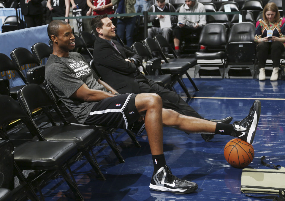 Photo - Brooklyn Nets center Jason Collins sits in a courtside seat after warming up for the Nets' NBA basketball game against the Denver Nuggets in Denver on Thursday, Feb. 27, 2014. (AP Photo/David Zalubowski)