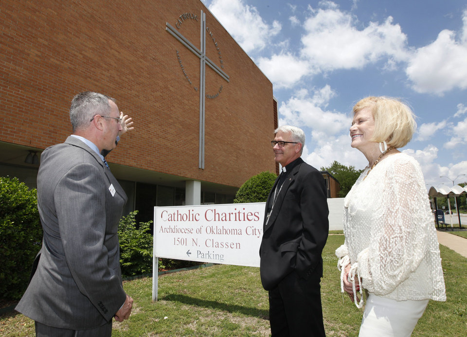Photo -  Patrick Raglow, left, executive director of Catholic Charities, Oklahoma City Archbishop Paul S. Coakley, and Crossbeam campaign co-chair Judy Love talk in front of the current Catholic Charities home on Thursday. Photo by Paul Hellstern, The Oklahoman   PAUL HELLSTERN -