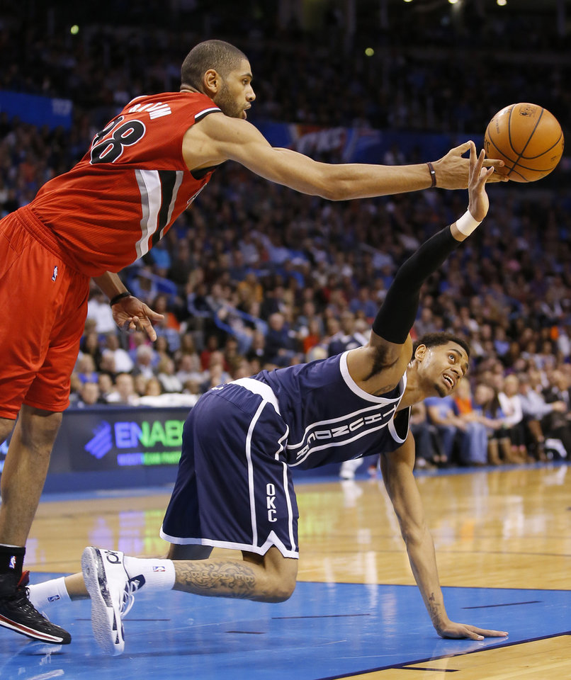 Photo - Portland's Nicolas Batum (88) tips a loose ball over Oklahoma City's Jeremy Lamb (11) during an NBA basketball game between the Oklahoma City Thunder and the Portland Trail Blazers at Chesapeake Energy Arena in Oklahoma City, Tuesday, Dec. 31, 2013. Oklahoma City lost 98-94. Photo by Bryan Terry, The Oklahoman