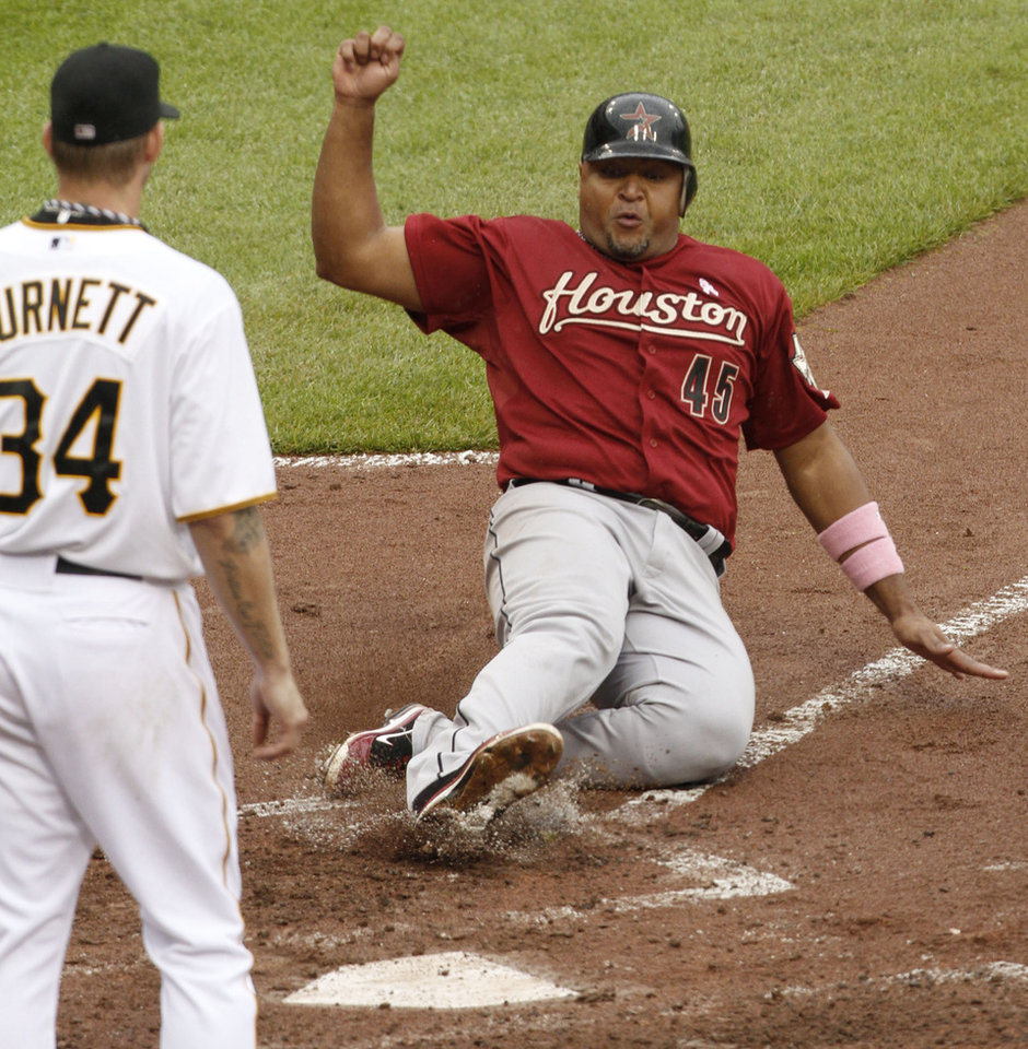 Photo -   Houston Astros' Carlos Lee (45) scores on a single by Chris Johnson as Pittsburgh Pirates starting pitcher A.J. Burnett (34) covers home in the seventh inning of the baseball game on Sunday, May 13, 2012, in Pittsburgh. The Pirates won 3-2 in 12 innings. (AP Photo/Keith Srakocic)