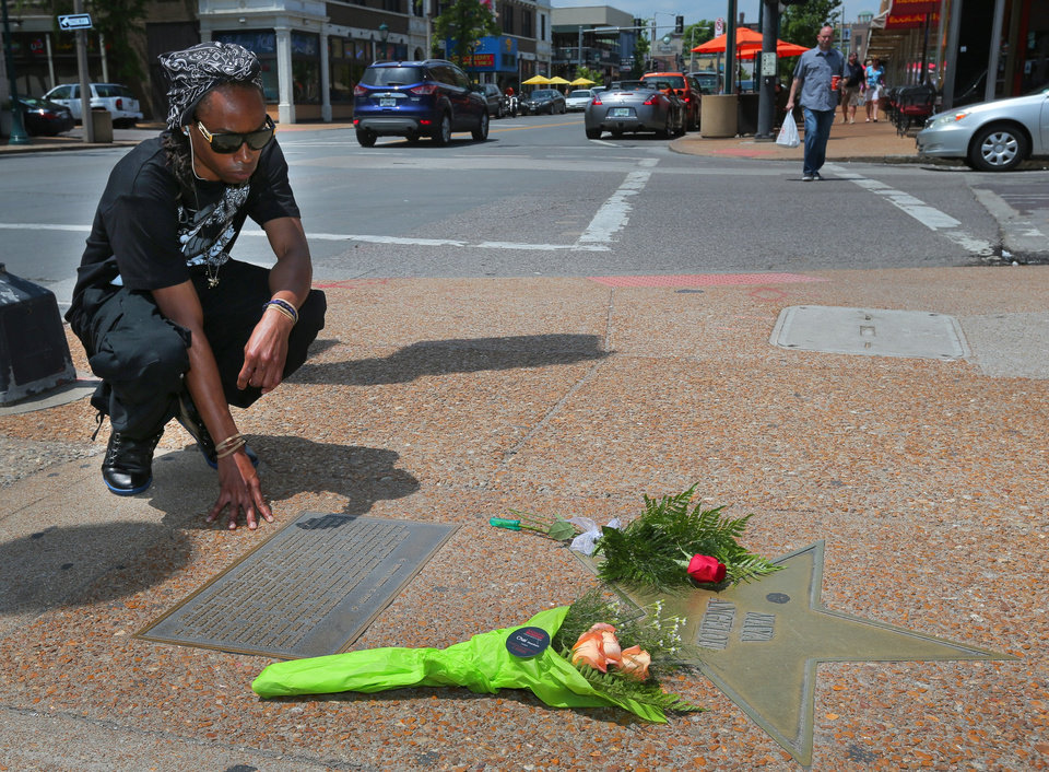 Photo - Quinntin Brown, 24, of St. Louis, pauses after laying a rose at Maya Angelou's star on the St. Louis Walk of Fame in The Loop in University City, Mo., Wednesday, May 28, 2014. Angelou, a Renaissance woman and cultural pioneer, has died Wednesday, her son said. She was 86. (AP Photo/St. Louis Post-Dispatch, David Carson)  EDWARDSVILLE INTELLIGENCER OUT; THE ALTON TELEGRAPH OUT