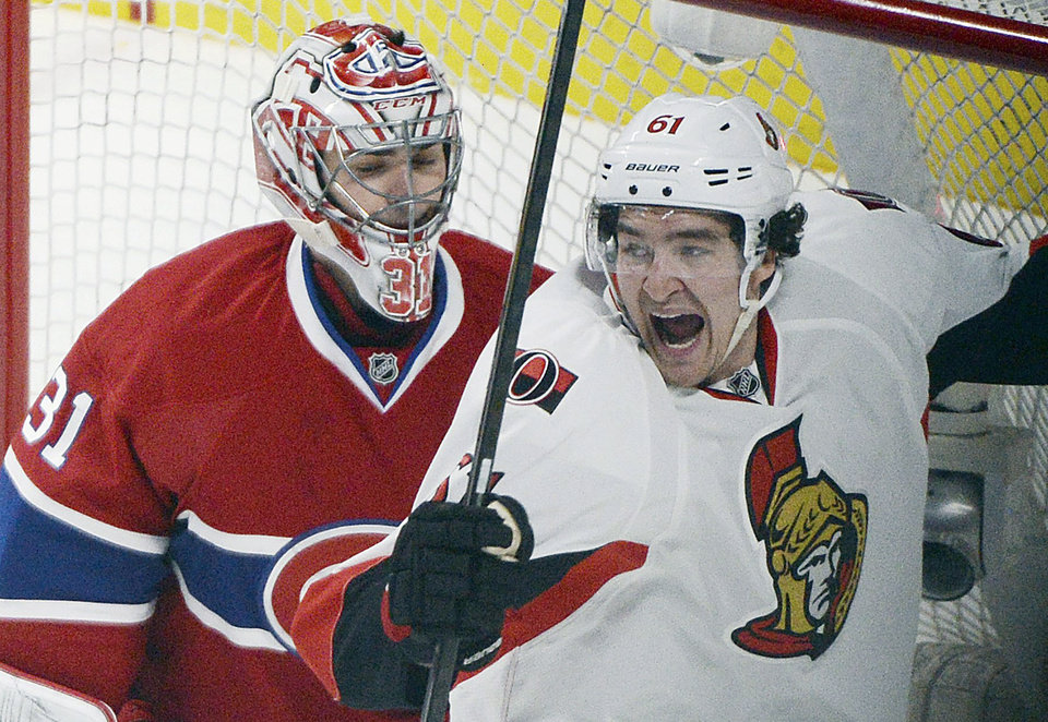 Photo - Ottawa Senators' Mark Stone, right, celebrates a goal by teammate Clarke MacArthur as Montreal Canadiens goaltender Carey Price is near during an overtime period of an NHL hockey game in Montreal, Saturday, Jan. 4, 2014. (AP Photo/The Canadian Press, Graham Hughes)