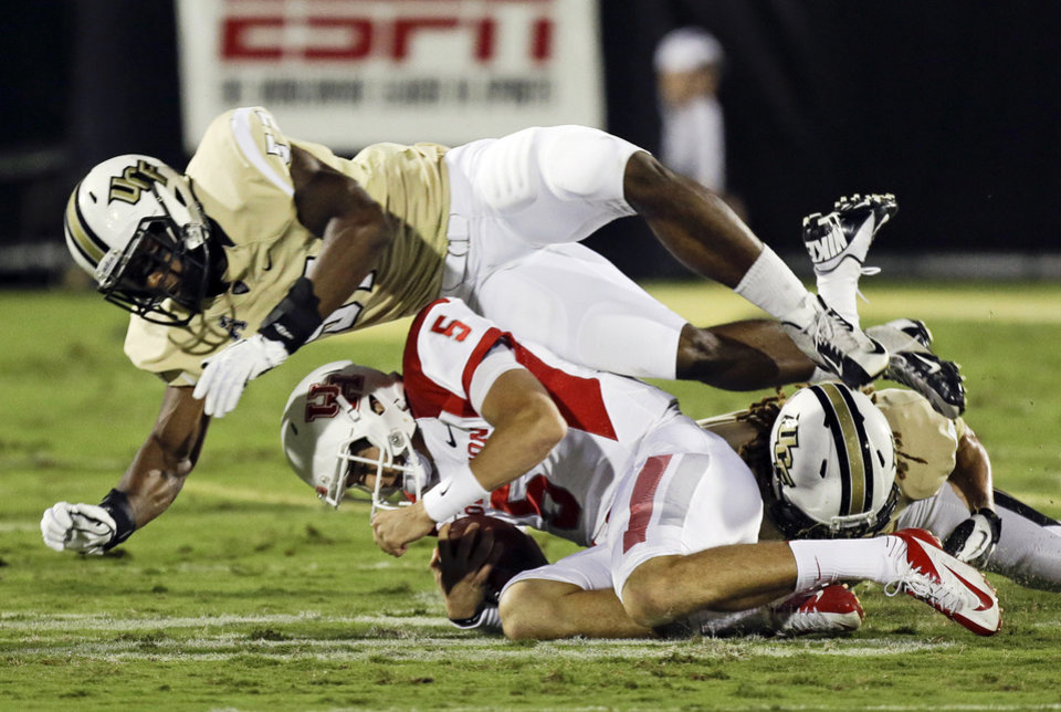 Photo - Houston quarterback John O'Korn (5) is tackled by Central Florida linebacker Troy Gray, top, and defensive back Jordan Ozerities, right, during the first half of an NCAA college football game in Orlando, Fla., Saturday, Nov. 9, 2013. (AP Photo/John Raoux)